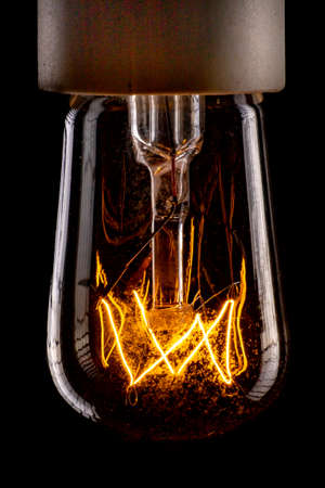 Traditional low-light filament bulb. Household lighting accessories. Dark background.