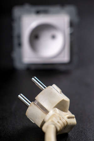 Electrical system plug and cable. Accessories for powering electrical devices. Dark background.