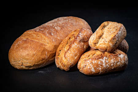 Fresh bread and rolls on a black kitchen table. Bread prepared for serving. Dark background.