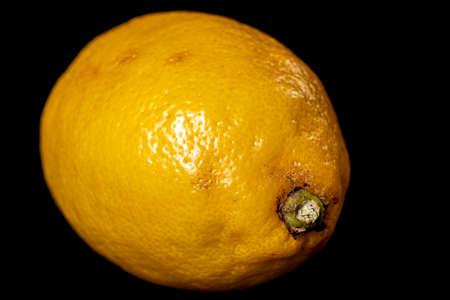 Fresh lemons on the black table. Citrus used to season dishes. Dark background.