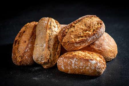 Fresh rolls on a black kitchen table. Bread prepared for serving. Dark background. Standard-Bild