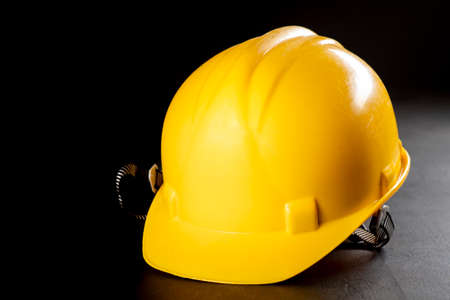 Yellow work helmet on a dark table. Protective accessories for construction workers. Dark background.