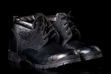 Black wet work boots on a dark table. Protective accessories for construction workers. Dark background.