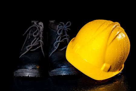 Black wet work boots and helmet on a dark table. Protective accessories for construction workers. Dark background.