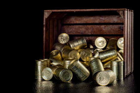 Wet metal cans in a wooden crate. Water droplets on metal food containers with a long shelf life. Dark background.