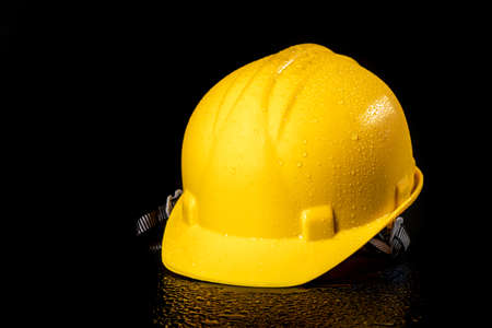 Yellow wet work helmet on a dark table. Protective accessories for construction workers. Dark background.