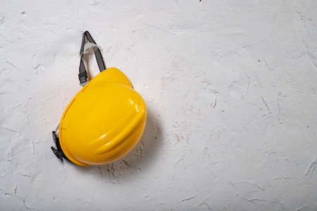 Yellow work helmet hung on a hook. Health and safety accessories on a white wall background. Light background. Standard-Bild