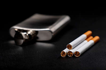Metal flask and cigarettes. Metal container for alcohol and smoking tobacco. Dark background.