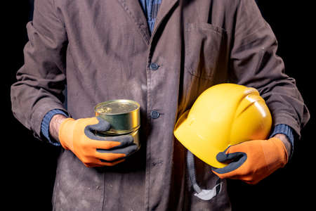A production worker with a canned meat with a helmet on his hands. A man with a food ration with a long shelf life. Dark background.