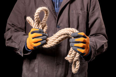 A production worker holding a thick rope in his hands. Construction worker working on the construction site. Dark background.