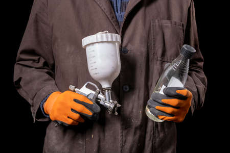 Varnisher with a paint gun in his hand. Car repair shop worker with tools. Dark background. Banque d'images