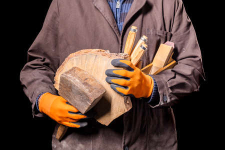 A carpenter with a piece of wood in his hands. A production worker in a workshop. Dark background. Banque d'images
