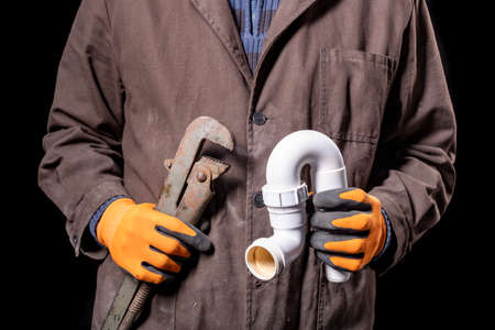 Plumber holding an adjustable wrench and a siphon to the wash basin. Worker repairing the hydraulic system. Dark background.