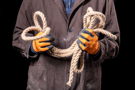 A production worker holding a thick rope in his hands. Construction worker working on the construction site. Dark background. Banque d'images