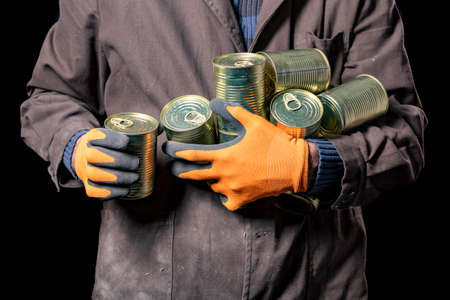 A production worker with canned meat. A man with a food ration with a long shelf life. Dark background. Banque d'images