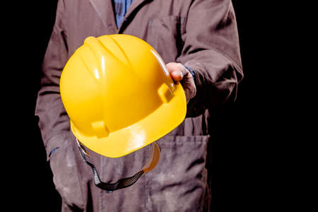 A production worker holding a yellow hard hat. Protective clothing in the workplace. Dark background.