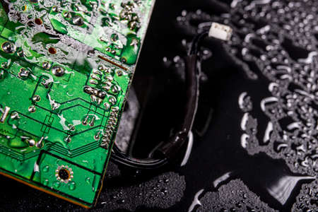 Wet circuit board with electrical paths. Water drops on an electronic device. Dark background.