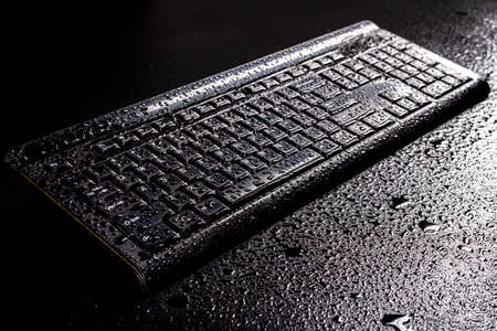 Wet keyboard from a personal computer. Water drops on an electronic device. Dark background.