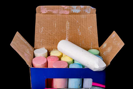 A box of colored chalk for street drawing. School chalk in a cardboard box. Dark background. Banque d'images