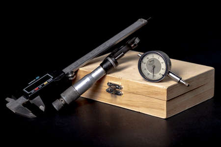 Wooden box with measuring tools. Accessories for mechanics and engineers. Dark background.