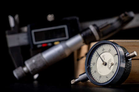 Dial gauge for surface measurement. Measurement accessories for engineers who conduct measurements. Dark background.