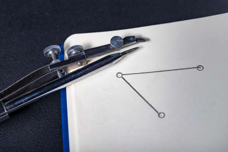 A metal Circinus arranged on a notebook. Accessories for drawing in a design office. Light background.