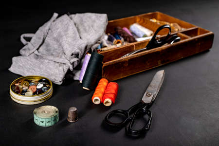 Utensils on the table in the tailor's workshop. Accessories necessary for tailoring. Dark background.