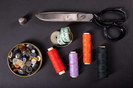 Threads on the table in the tailor's workshop. Accessories necessary for tailoring. Dark background.