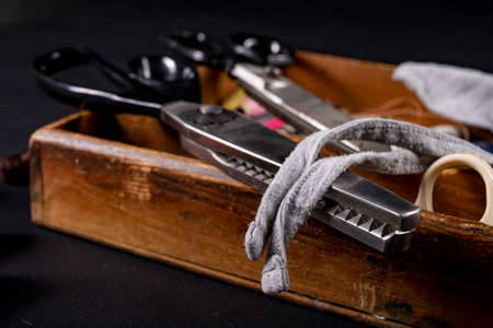 Scissors on the table in the tailor's workshop. Accessories necessary for tailoring. Dark background.