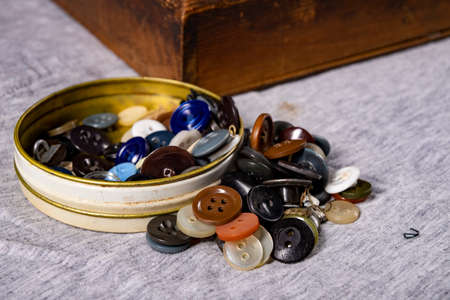 Buttons on the table in the tailor's workshop. Accessories necessary for tailoring. Dark background.
