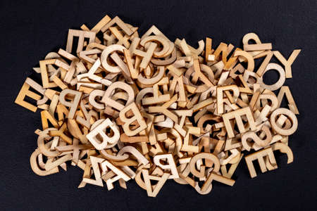 A stack of small wooden letters on a dark table. Letters outlines for arranging inscriptions and words. Dark background.