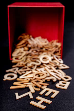 Small wooden letters spilling out of a red box. Outlines of letters with a wood texture used to form words. Dark background.