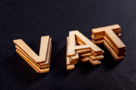 VAT inscription made of small wooden letters. A word for tax. Dark background. Banque d'images