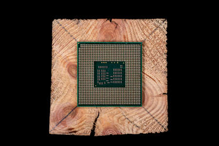 A personal computer processor stacked on raw wood. Accessories and spare parts for computer repair. Dark background.