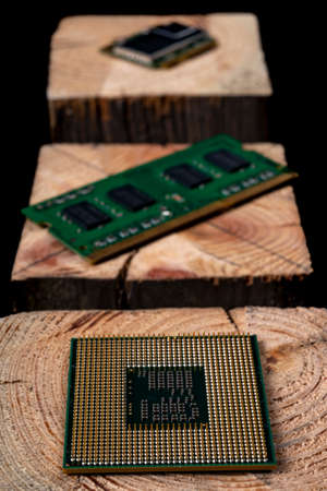 Processor and RAM memory from a personal computer stacked on raw wood. Accessories and spare parts for computer repair. Dark background.