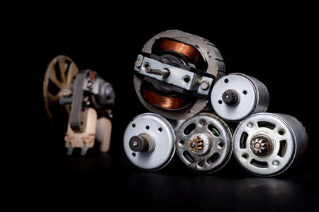 Small electric motors for driving domestic appliances. Electric devices stacked on a table. Dark background. 스톡 콘텐츠