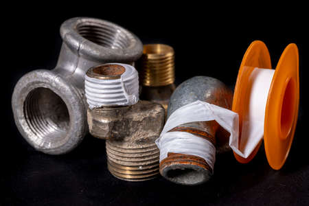 Plumbing fittings and accessories. Pipe connections with Teflon tape. Dark background.