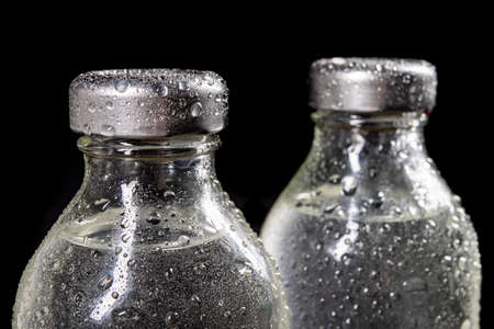 Glass bottles with fresh drinking water. Water drops on glass containers for water storage. Dark background.