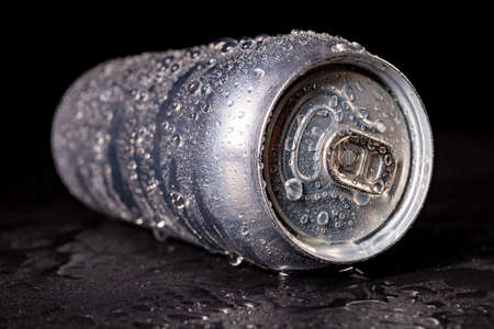 A wet can of a cold and tasty drink. Water drops on the metal surface of the metal container. Dark background. 스톡 콘텐츠