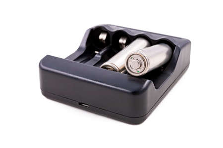 Black charger and silver batteries for energy storage. Accessories for powering household appliances. Light background.