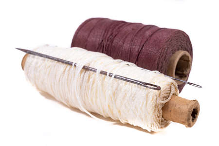 Strong twine and old heavy tailoring needles. Accessories used in a leathercraft workshop. Light background.