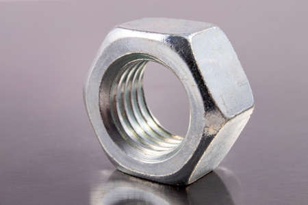 Metal nut with metric thread. Metal accessories for assembling metal parts. Dark background.