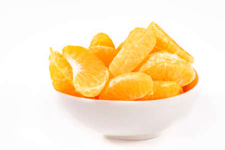 Tangerines, peeled in quarters. Citrus fruits arranged in a porcelain bowl. Light background.