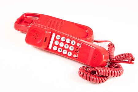 Red analog telephone for making calls. Old electronic accessories used at home and in the office. Light background.