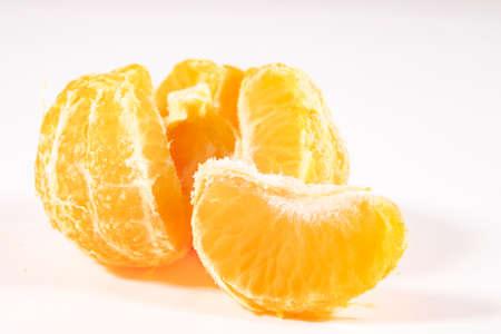 Tasty tangerine peeled. Citrus fruits used in desserts. Light background.