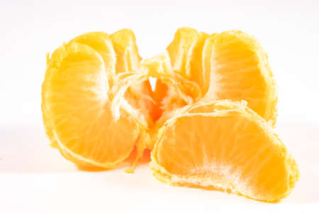Tangerines, peeled in quarters. Citrus fruits used in desserts. Light background.