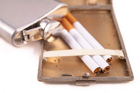 Metal flask and cigarettes. Metal container for alcohol and smoking tobacco. Light background.