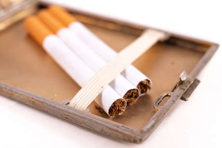 Cigarettes in a metal cigarette case. Stimulants for adults dangerous to health. Light background.