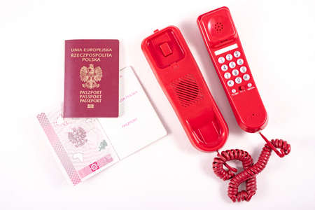 Passport and old red telephone camera. Voice communication accessories and personal documents. Light background. 스톡 콘텐츠