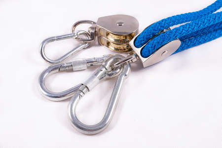 Rope, carabiner and sailing pulley. Accessories used on a deep sea yacht. Light background.